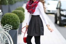 With white shirt, printed skirt, pumps and red bag
