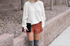 With white sweatshirt, gray suede over the knee boots and black clutch