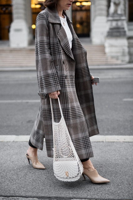 With white t-shirt, black trousers, beige heels and checked maxi coat