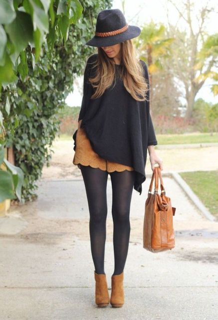 With wide brim hat, black loose blouse, black tights, brown suede ankle boots and brown leather tote