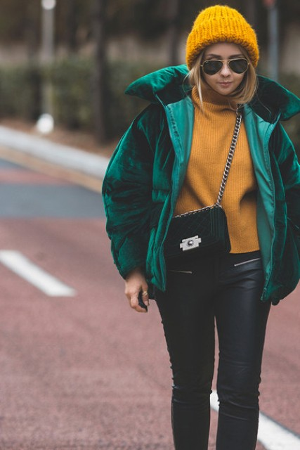 With yellow sweater, yellow hat, black leather pants and small bag