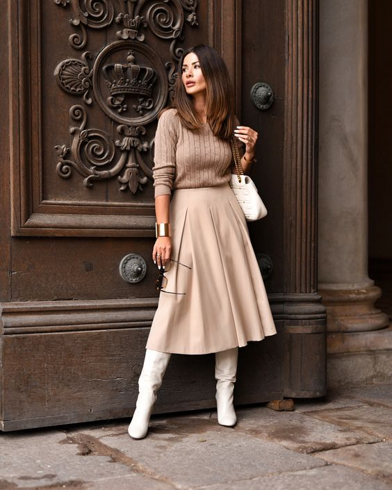 a beige cable knit sweater, a neutral pleated A-line midi, white boots, a white bag bring a romantic touch