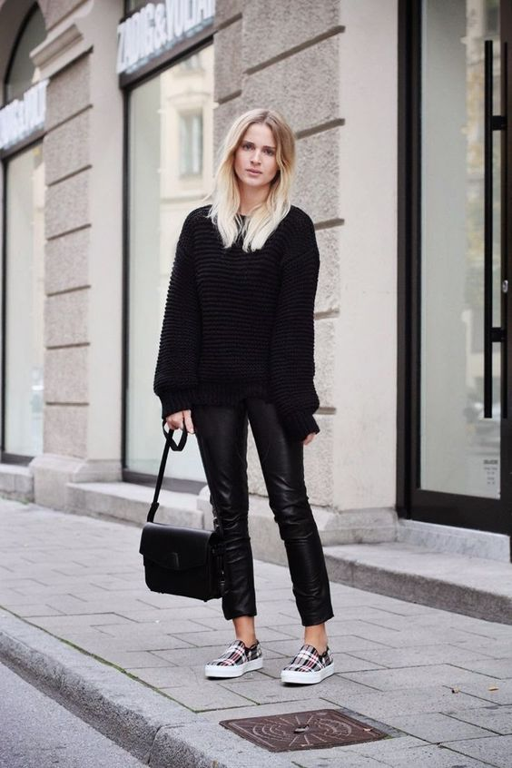 a black chunky knit sweater, black cropped pants, plaid slipns and a black bag