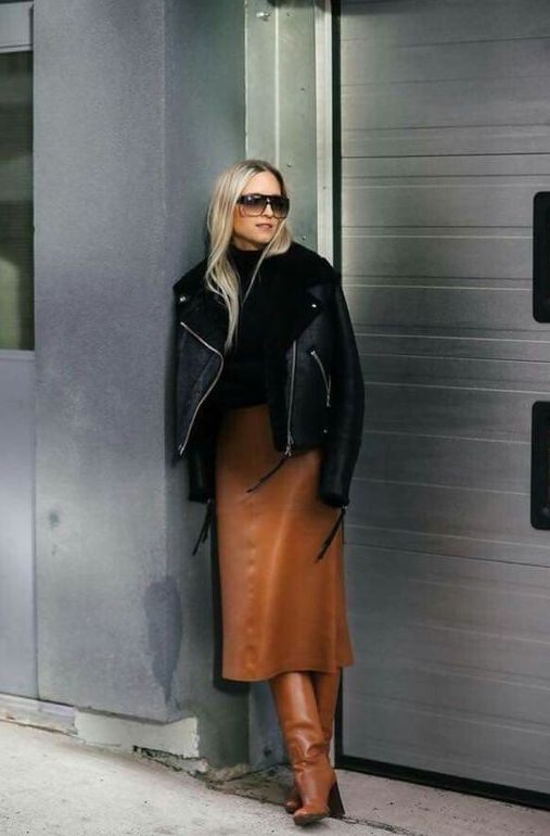 a black turtleneck, a rust midi leather skirt, matching boots, a black shearlign coat for an edgy touch