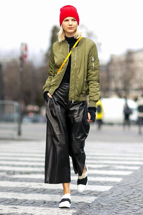 a black turtleneck, black cropped culottes, a green bomber jacket, blakc and white slipons and a beanie