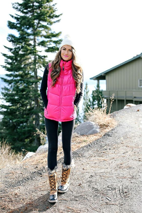 a black turtleneck, blakc leggings, faux fur boots, a hot pink puffer vest and a white beanie for a glam feel