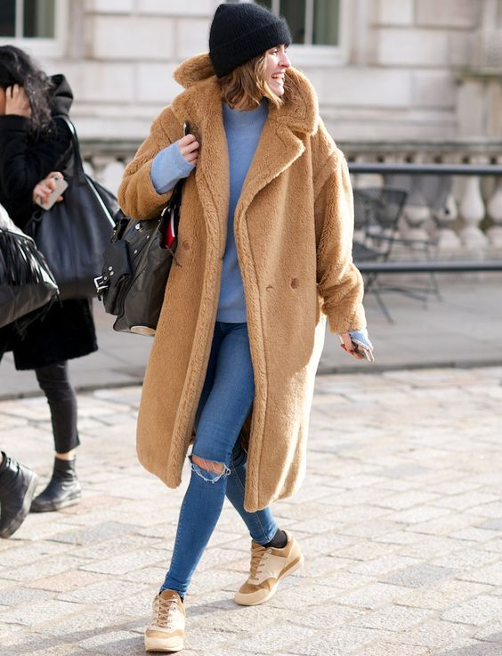 a blue sweatshirt and skinnies, neutral sneakers, a black beanie and a camel teddy bear coat