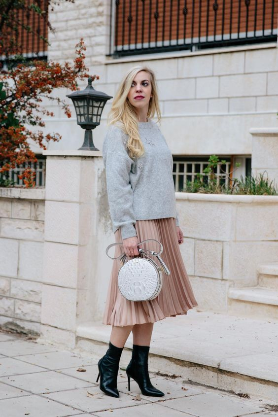 a blush pleated skirt, a grey sweater, black sock boots and a grey metallic bag with a shiny touch