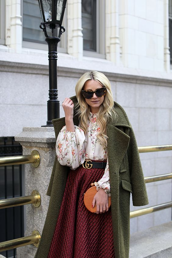 a floral blouse, a burgundy tweed A-line midi skirt, a green coat and a round orange bag