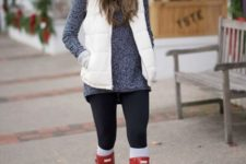 a grey sweater, black leggings, white leg warmers, red rubber boots, a white puffer vest and a white beanie