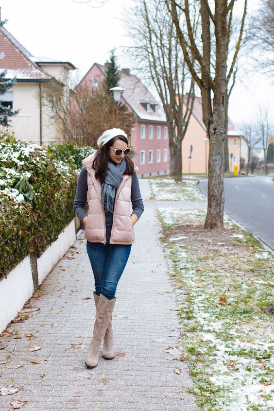 a grey turtleneck, blue jeans, a grey scarf, a white beret, a blush puffer vest and blush knee boots
