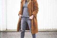 a grey turtleneck, grey ripped skinnies, grey slipons, a grey beanie and an amber teddy bear coat