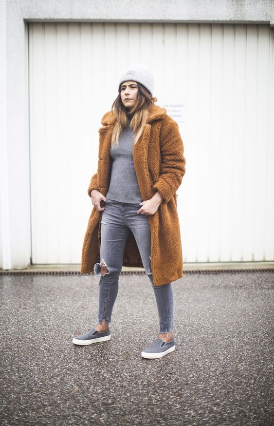 a grey turtleneck, grey ripped skinnies, grey slipons, a grey beanie and an amber teddy bear coat