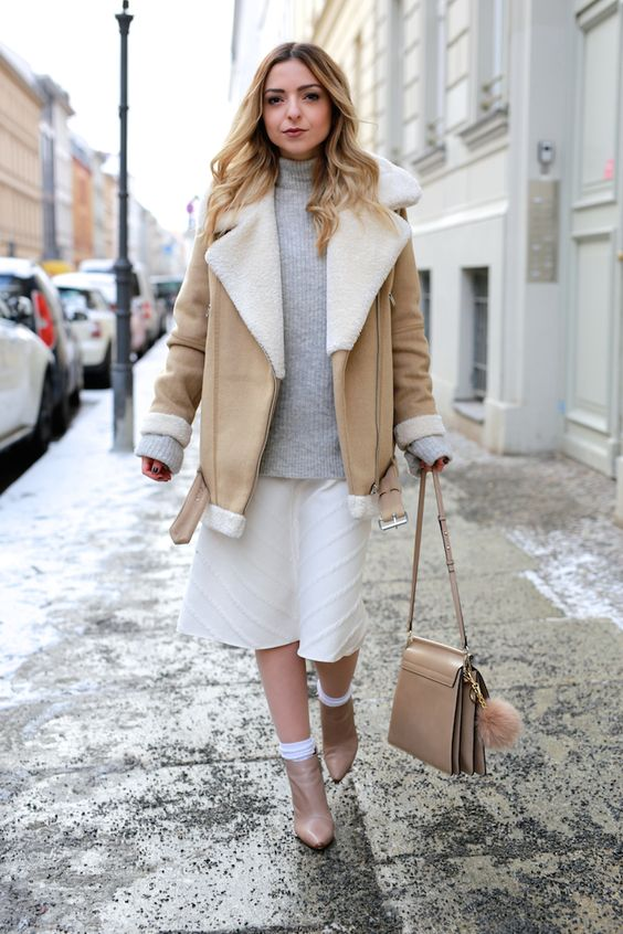 a grey turtleneck sweater, a creamy patterned skirt, a neutral shearling coat, neutral boots and a matching bag