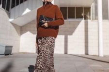 a leopard midi skirt, a rust turtleneck sweater, black boots and a black clutch to enjoy colors