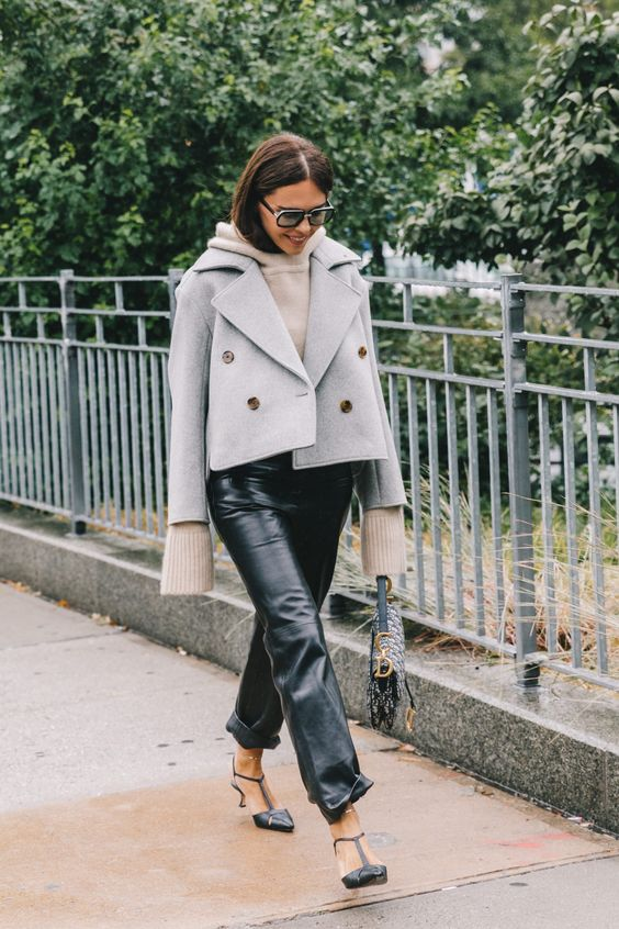 a neutral hoodie, black leather cropped pants, black shoes and a grey cropped coat