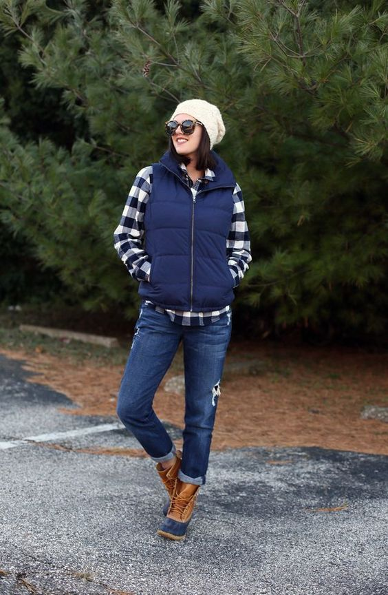 a plaid shirt, a navy puffer vest, navy boyfriends, warm winter boots and a white beanie