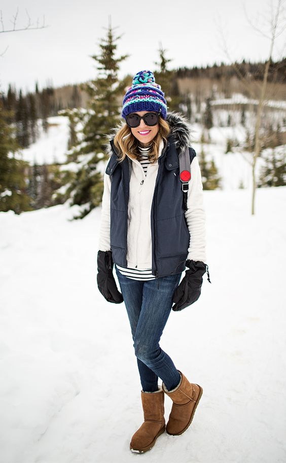 a snowy winter outfit with a striped top, a creamy hoodie, a black puffer vest, navy skinnies, ugg boots, a colorful beanie