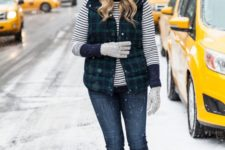 a striped sweater, navy jeans, a plaid puffer vest, navy boots, grey gloves and a white beanie