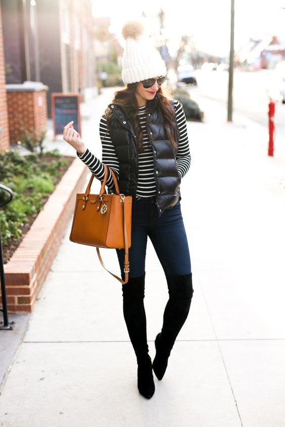 a striped top, navy skinnies, tall black boots, a black puffer vest, a white beanie and an amber bag