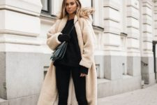 a total black look with a sweater, skinnies, embellished booties and a creamy teddy bear coat