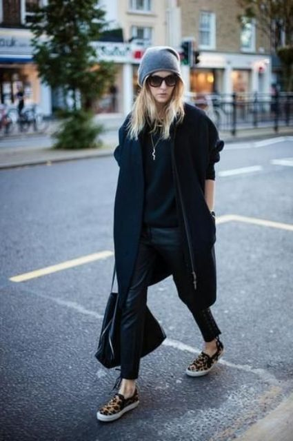 a total black look with cropped pants, a sweater, a coat, leopard print slipons, a grey beanie and a bag
