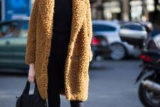 a total black look with skinnies, a long sleeve top, boots and a brown teddy coat