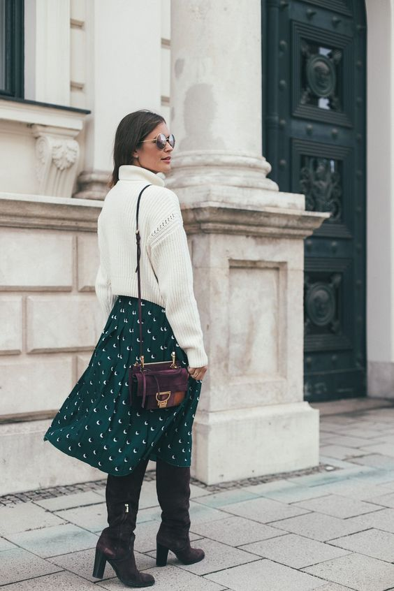 a white oversized sweater, a green polka dot midi skirt, plum-colored boots and a matching bag