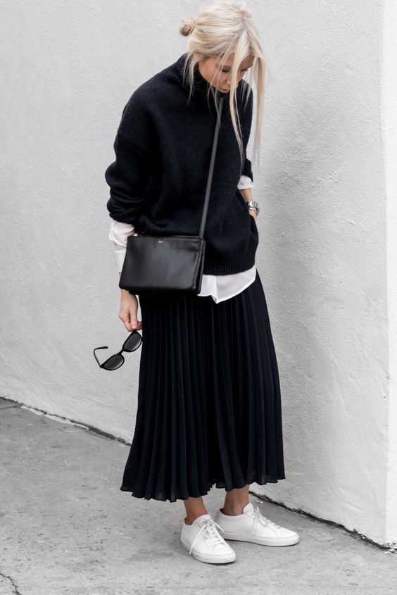 a white shirt, a black sweater over it, a black pleated midi skirt, white sneakers and a black bag