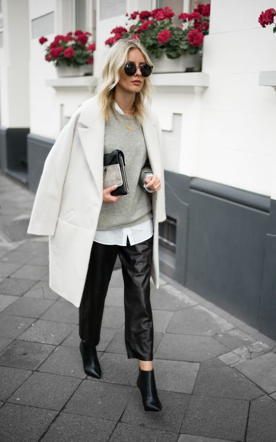 a white shirt, a grey sweater, a creamy coat, blakc cropped pants, black booties and a clutch