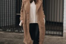 a white sweater, black leather pants, brown winter boots and a brown teddy coat