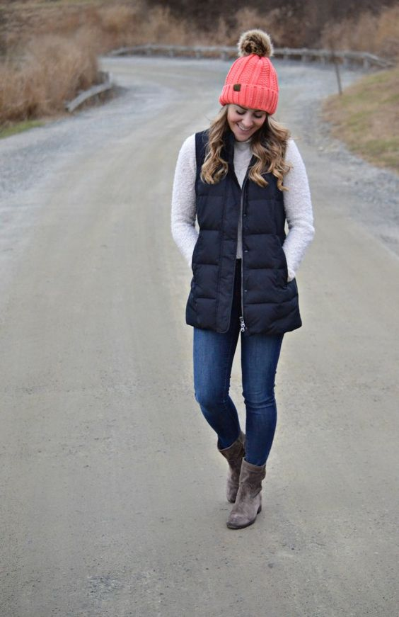 a white sweater, blue jeans, a black puffer vest, grey booties and a coral beanie