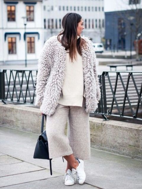 a white sweater, neutral cropped culottes, white sneakers and a neutral chunky teddy coat with a black bag