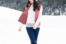 a white top with lace trim, blue jeans, a dusty pink puffer vest, beige fur boots, a white beanie