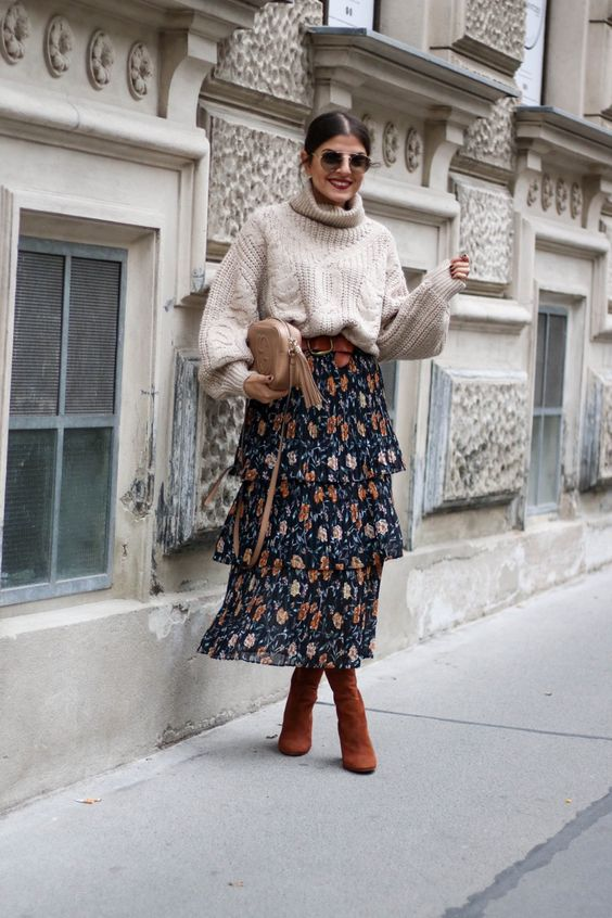 an oversized cable knit neutral sweater, a moody floral midi skirt, rust boots and a neutral bag