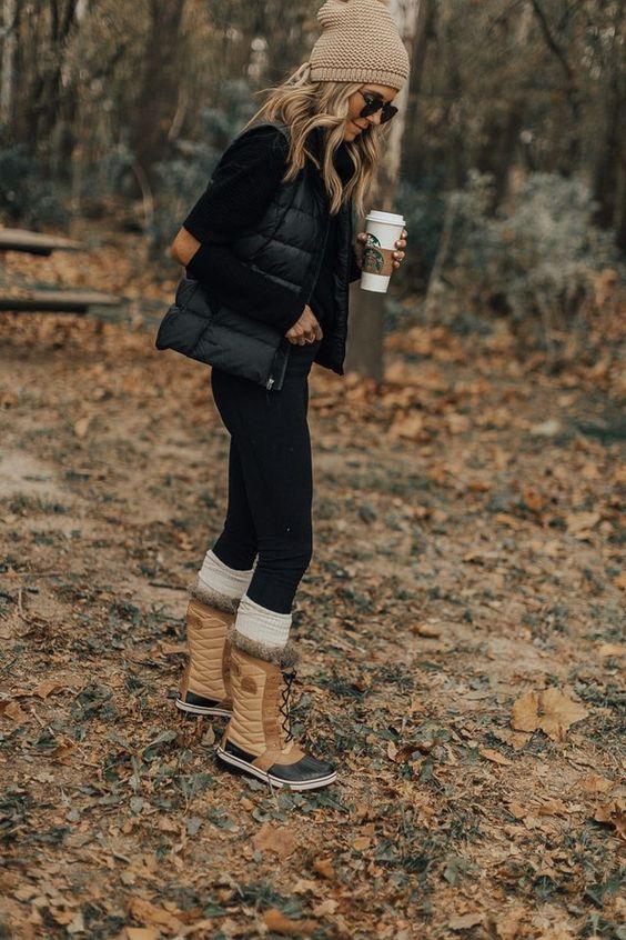 black jeans, a black turtleneck, a black puffer vest, a beige beanie, beige fur boots