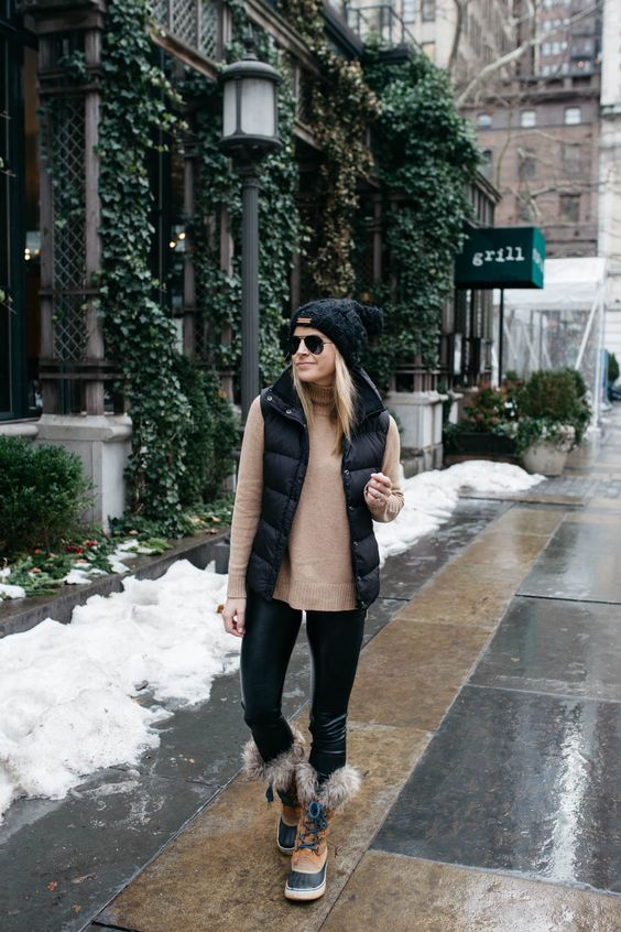 black leather pants, a beige turtleneck sweater, a black puffer vest, a black beanie, faux fur boots