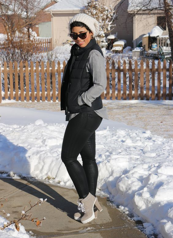 black waxes jeans, grey booties, a grey shirt, a black puffer vest, a creamy beanie