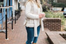 blue ripped jeans, a creamy cable knit sweater, a creamy puffer vest, beige knee boots and a creamy scarf