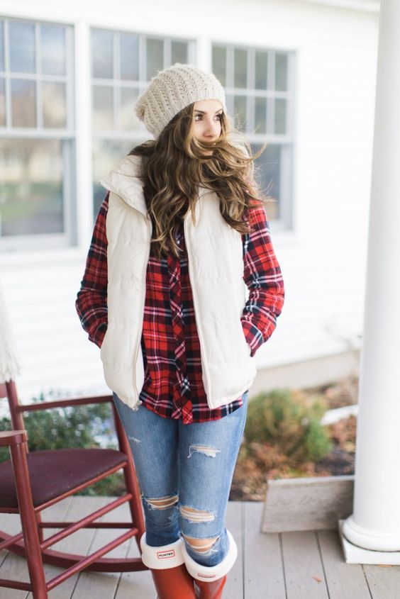 blue ripped jeans, a plaid shirt, a white puffer vest, a cremay beanie for a comfy holiday look