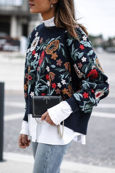 blue skinnies, a white shirt, a floral embroidered sweatshirt and a clutch, just add a coat