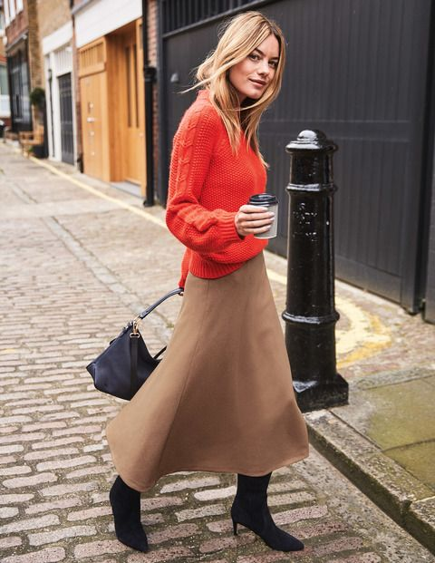 compose a bright winter outfit of a beige midi skirt, a coral sweater, black boots and a black bag