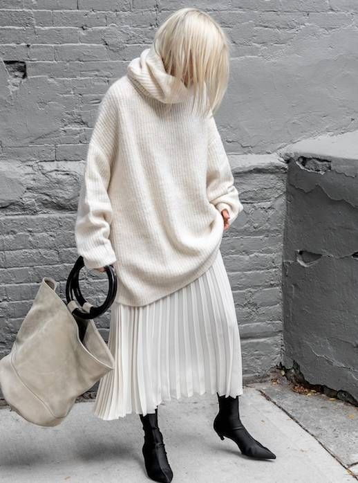 creamy oversized sweater, a creamy pleated midi skirt, black sock boots and a neutral oversized bag