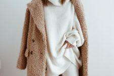 white pants, a white oversized turtleneck sweater, a camel teddi coat