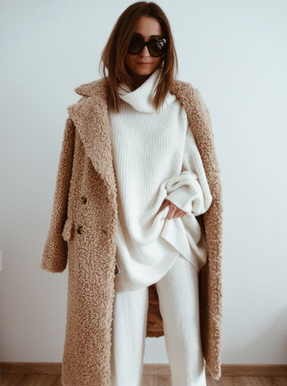 white pants, a white oversized turtleneck sweater, a camel teddi coat