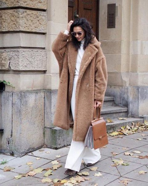 white pants, a white turtleneck, leopard print boots, a brown teddy bear coat and a brown bag