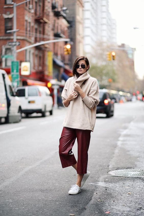 white sneakers, a neutral oversized cashmare sweater, burgundy cropped leather pants