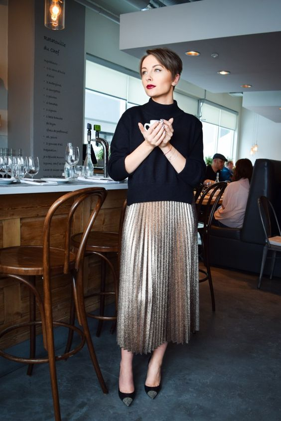 a black turtleneck, a metallic pleated midi skirt, black shoes with glitter touches
