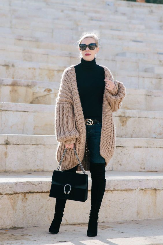 a black turtleneck, navy skinnies, tall black boots, a chunky knit long cardigan and a stylish bag