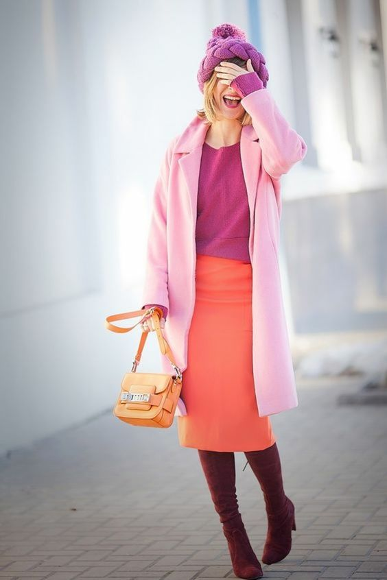 a colorful winter outfit with a pink sweatshirt, a coral midi skirt, a light pink coat, a pink beanie and plum-colored boots